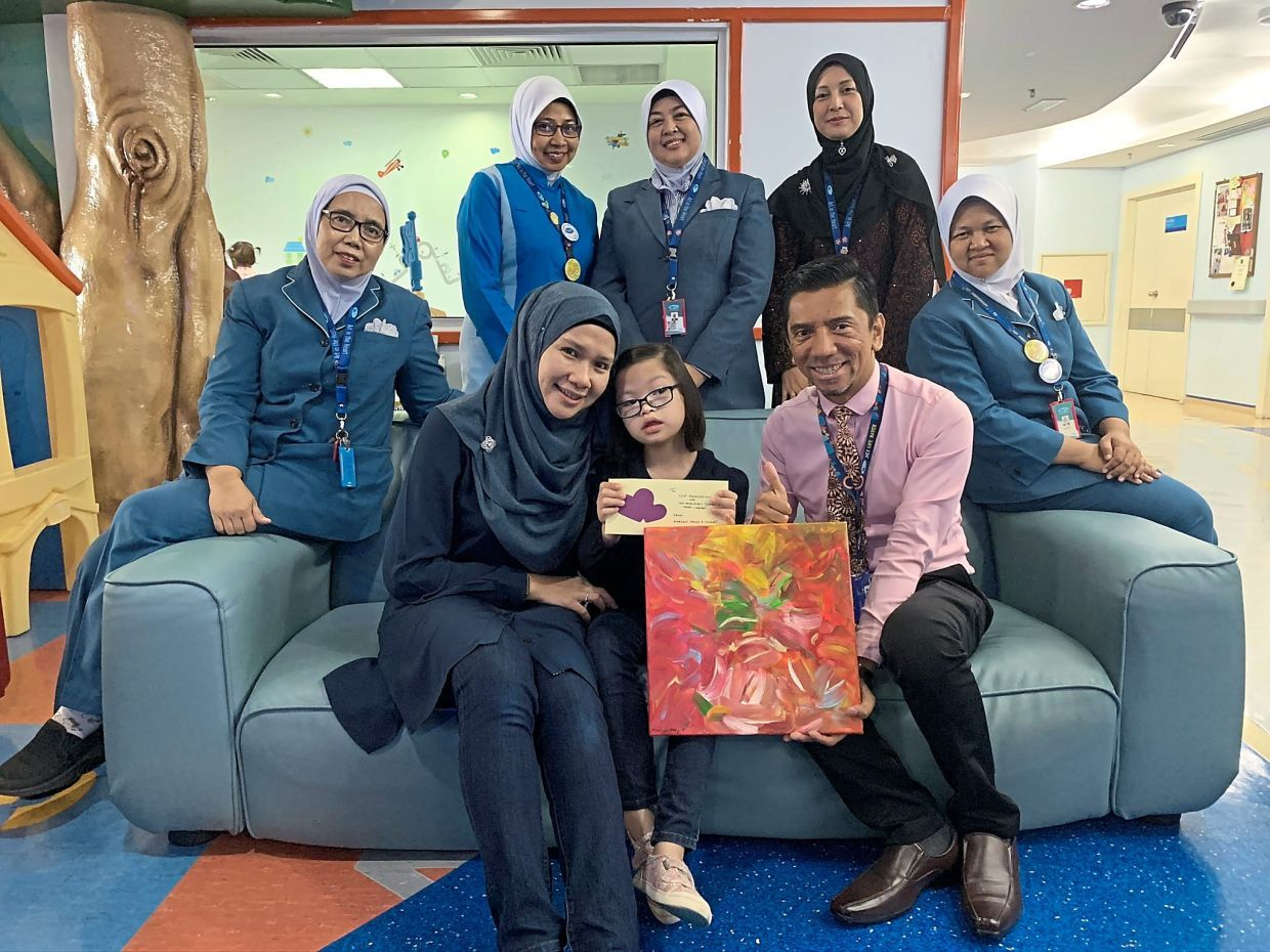 Institut Jantung Negara's Dr Marhisham Che Mood  (right, seated) receiving Maryam's painting and donation to aid children in need of a heart surgery. — SHARIFAH SARAH SYED MOHAMED TAHIR