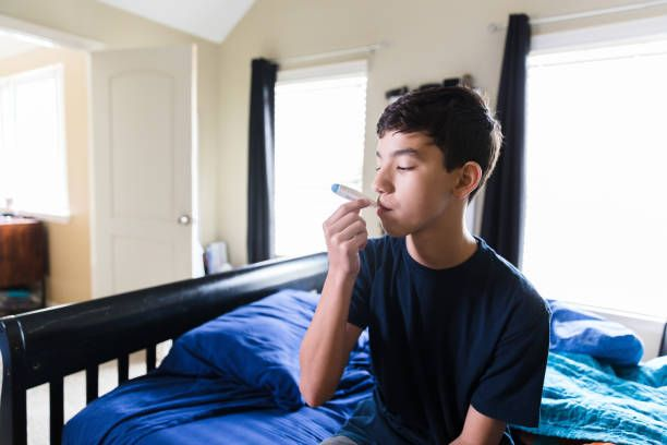 When the teen boy wakes up sick in the morning, he takes his temperature with a digital thermometer.